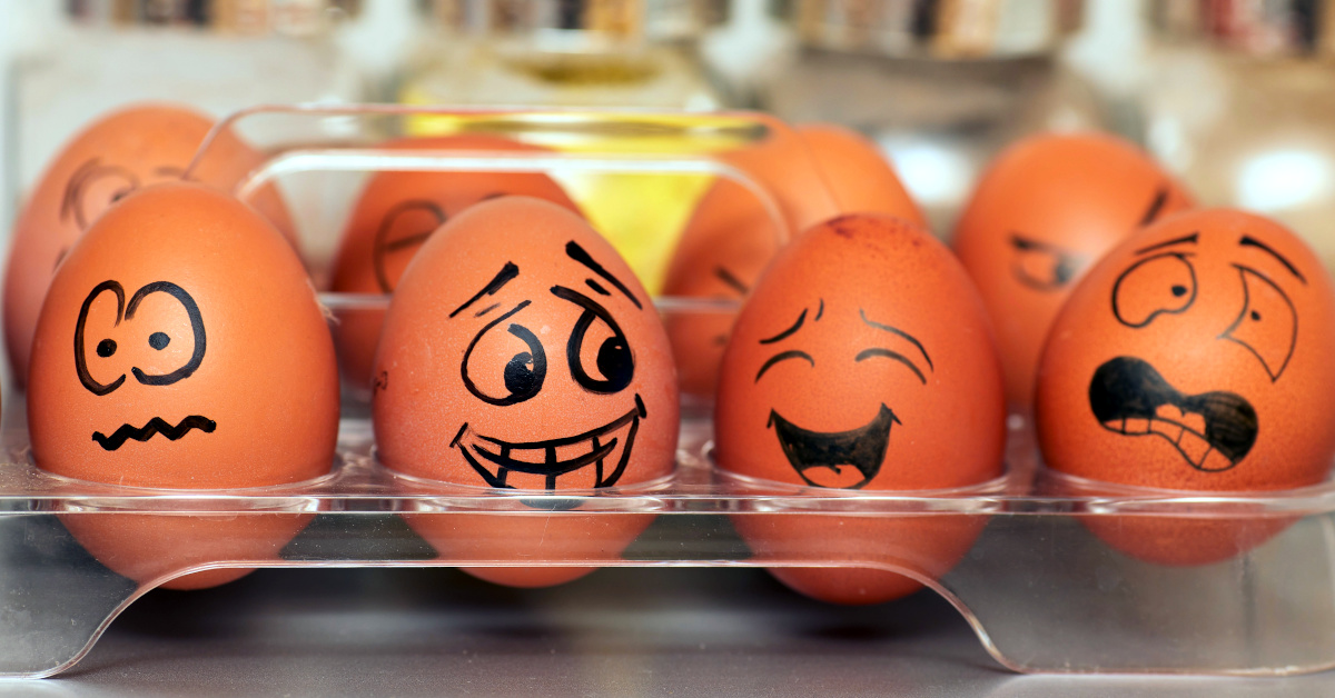 Eggs painted with a sharpie, bearing faces displaying various emotions. Arranged in an egg holder from a fridge.